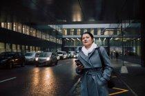 Підприємець з мобільного телефону озираючись, стоячи на міській вулиці — стокове фото