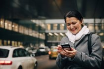 Улыбаясь бизнес-леди с помощью смартфона, стоя на городской улице против здания — стоковое фото