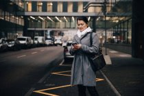 Businesswoman using smart phone while standing on city street against building — Stock Photo