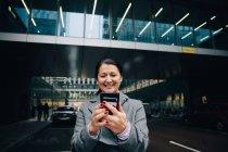 Femme d'affaires souriante utilisant un téléphone portable tout en se tenant sur la route contre la construction dans la ville — Photo de stock