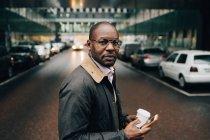 Портрет бизнесмена с кофе с помощью мобильного телефона, стоя на улице в городе — стоковое фото