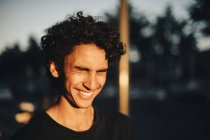 Adolescente alegre com os olhos fechados na cidade durante o pôr do sol — Fotografia de Stock