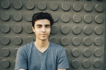 Portrait of confident young man standing against wall — Stock Photo
