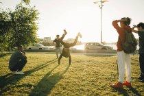 Друзья смотреть подростка делают стойку на поле в Солнечный день — стоковое фото