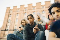Низький кут зору чоловічого друзів, сидячи в місті — стокове фото