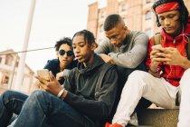 Amigos masculinos usando teléfonos móviles mientras están sentados en la ciudad - foto de stock