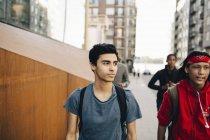 Amigos homens andando na calçada na cidade — Fotografia de Stock
