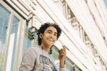 Visão de ângulo baixo de adolescente alegre ouvindo música em fones de ouvido contra a construção na cidade — Fotografia de Stock