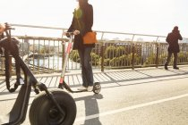 Los viajeros en el puente contra el cielo en la ciudad - foto de stock