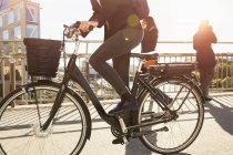 Sección baja de mujer madura montando bicicleta eléctrica por los viajeros en el puente en la ciudad contra el cielo - foto de stock