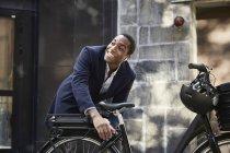 Sorridente giovane pendolare maschio che blocca la bicicletta elettrica mentre guarda lontano contro l'edificio in città — Foto stock