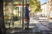 Vista laterale a tutta lunghezza del giovane pendolare maschio che utilizza lo smart phone mentre tiene in mano un monociclo elettrico alla fermata dell'autobus in città — Foto stock