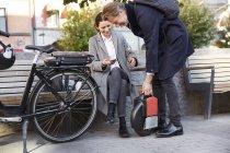 Sorridente donna matura seduto sulla panchina guardando l'uomo che tiene monociclo elettrico in città — Foto stock