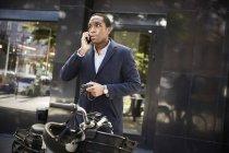 Giovane pendolare di sesso maschile che parla su smart phone mentre in piedi con la bicicletta elettrica contro l'edificio in città — Foto stock