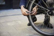 Bassa sezione di pendolare maschio bloccaggio ruota bicicletta elettrica contro edificio in città — Foto stock