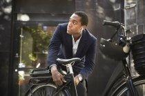 Giovane pendolare maschio che blocca la bicicletta elettrica mentre guarda lontano contro l'edificio in città — Foto stock