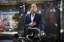Sorridente giovane pendolare maschile utilizzando smart phone mentre in piedi con bicicletta elettrica contro edificio in città — Foto stock