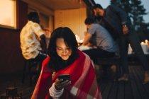 Souriant jeune femme utilisant le téléphone portable tandis que les amis en arrière-plan pendant le dîner — Photo de stock