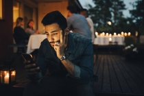 Man using mobile phone while friends in background during dinner party — Stock Photo