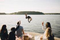 Uomini e donne che guardano amico a torso nudo tuffarsi dal molo al lago contro il cielo — Foto stock