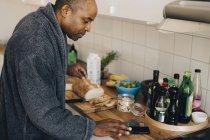 Hombre maduro usando el teléfono inteligente en el mostrador de la cocina en casa - foto de stock