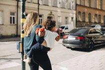 Madre che porta la figlia mentre cammina sul sentiero in città — Foto stock