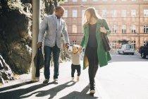 Comprimento total de pais multi-étnicos segurando as mãos da filha enquanto caminhava no caminho da cidade — Fotografia de Stock