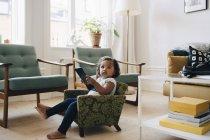 Comprimento total da menina segurando tablet digital enquanto sentado em poltrona pequena em casa — Fotografia de Stock