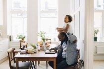 Отец несет веселую дочь на плече во время работы на ноутбуке в доме — стоковое фото