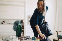 Femme adulte moyenne mettant tablette numérique dans le sac à la maison — Photo de stock