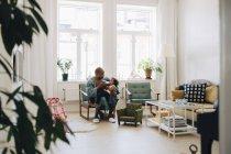 Lunghezza completa del padre che alimenta il latte alla figlia mentre è seduto in soggiorno a casa — Foto stock