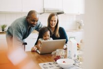 Smiling parents looking at daughter playing with laptop in dining room — Stock Photo