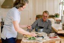 Vista lateral de la cuidadora femenina está sirviendo comida en la mesa para un anciano jubilado sentado en un asilo de ancianos - foto de stock
