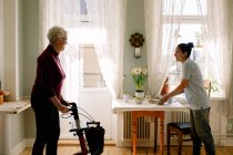 Smiling young female caregiver serving breakfast while looking at retired senior woman walking with rollator in nursing — Stock Photo