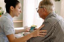 Jovem assistente social feminina assistindo aposentado homem com telefone inteligente em casa de repouso de enfermagem — Fotografia de Stock