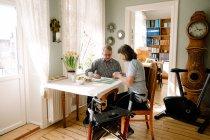 Зрелая женщина-медработница играет в карты с пожилым мужчиной за столом в доме престарелых — стоковое фото