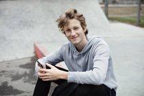 Retrato do adolescente de sorriso que prende o telefone esperto ao sentar-se na cidade — Fotografia de Stock