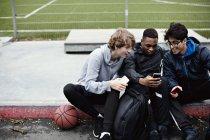 Amigos masculinos que usam telefones móveis ao sentar-se no passeio após a prática do basquetebol durante o inverno — Fotografia de Stock