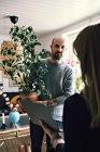 Уверенный мужчина, несущий горшок с растением, смотрит на женщину, стоящую с ноутбуком в комнате — стоковое фото