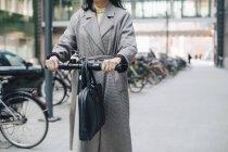 Midsection de femme d'affaires équitation scooter électrique push sur le sentier piétonnier en ville — Photo de stock