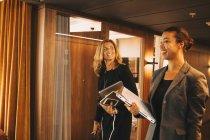 Advogadas sorridentes com arquivos discutindo no corredor no escritório — Fotografia de Stock