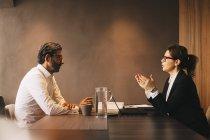 Vista laterale dell'avvocato donna che spiega il cliente maturo in riunione in ufficio — Foto stock