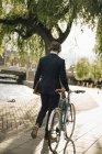 Vue arrière d'un homme d'affaires marchant à vélo sur un sentier pédestre en ville — Photo de stock