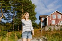 Улыбающаяся женщина среднего возраста разговаривает по мобильному телефону, стоя напротив деревьев и дома — стоковое фото