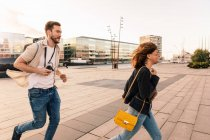 Happy couple running on street while exploring city — Stock Photo