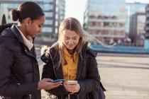 Ragazze adolescenti sorridenti che utilizzano i telefoni cellulari mentre in piedi in città durante la giornata ventosa — Foto stock