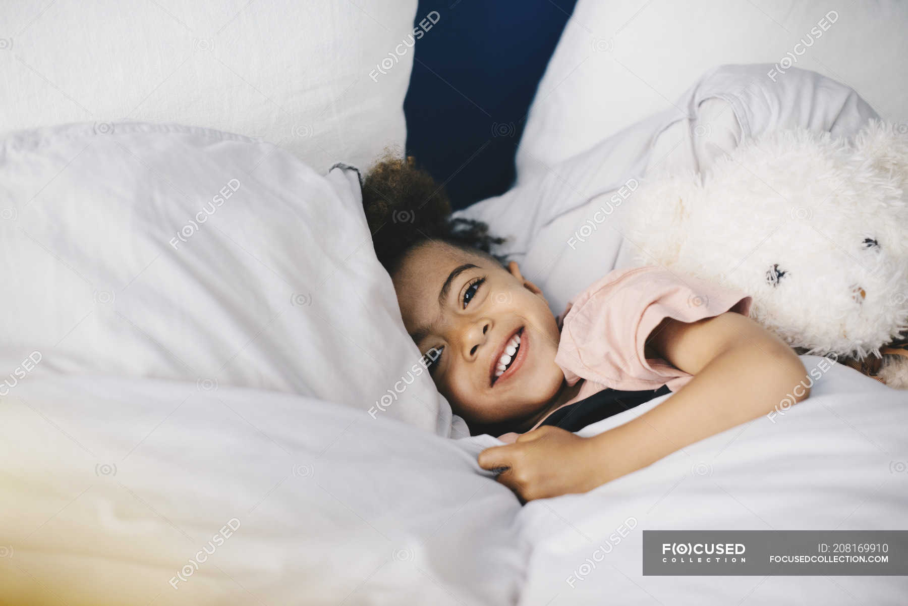 0362e870b Portrait of smiling boy lying with teddy bear on bed at home ...