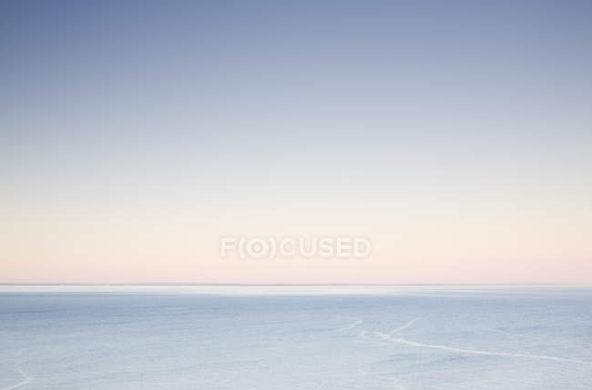 Спокійна океан води та узбережжя на горизонті на світанку — стокове фото