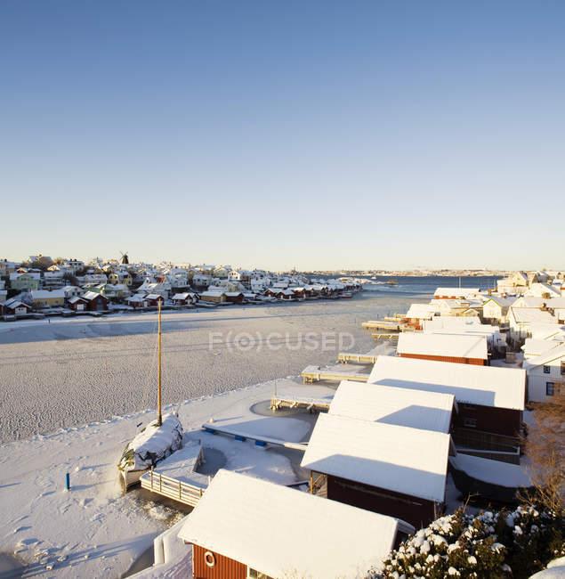 Case innevate vicino al fiume ghiacciato in Lysekil, Bohuslan, Svezia — Foto stock