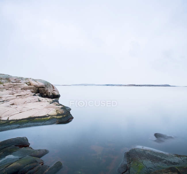 Rock by sea under cloudy blue sky — Stock Photo